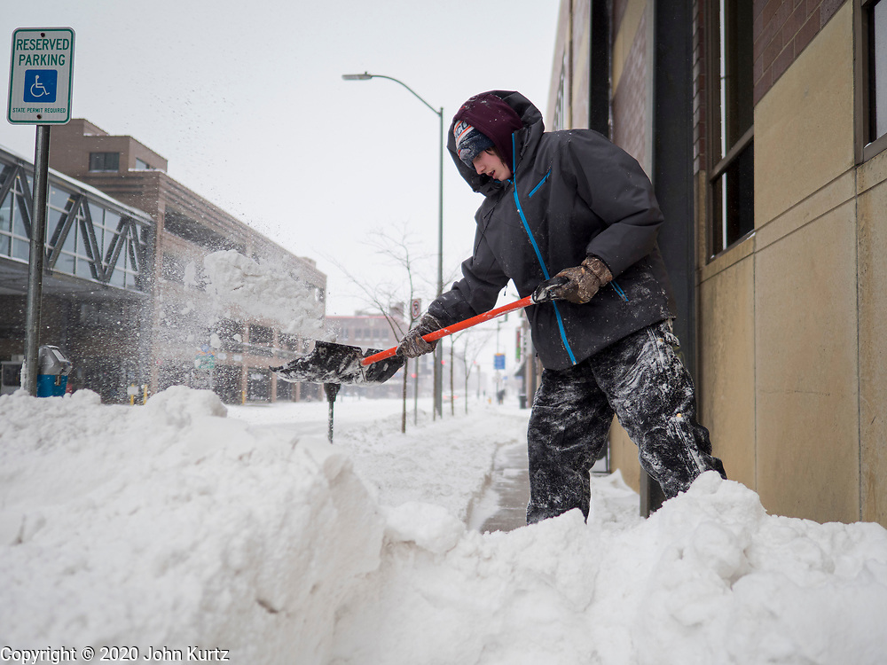 17 JANUARY 2020 - DES MOINES, IOWA: A worker shovels a snow packed sidewalk in the Court District of Des Moines. The second significant snow fall in a week hit central Iowa Friday. The snow started falling during the morning rush hour and by early afternoon about five inches had fallen in Des Moines. Meteorologists said up to 1/10 of an inch of ice could cover the snow by the end of the day. The snowstorm was expected to turn into a blizzard in northern Iowa on Saturday with wind speeds above 30MPH. Many businesses in the Des Moines area closed early Friday and several of the Democratic presidential candidates cancelled their campaign events because of the snow.  PHOTO BY JACK KURTZ