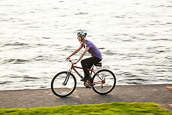 United States, Washington, Kirkland, woman bicylclng next to Lake Washington.  MR