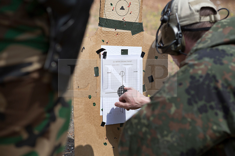 © Licensed to London News Pictures. 30/03/2015. Erbil, Iraq. An German Army officer checks the grouping shot by a peshmerga fighter during a training package run by coalition forces tutors at a military training area near Erbil, Iraq.<br /> <br /> The training is part of a four week long package, the first to be held with a complete peshmerga battalion, run by coalition forces mobile training teams (MTT) in Kurdistan with the aim to make the peshmerga more efficient in combatting the Islamic State. Photo credit: Matt Cetti-Roberts/LNP