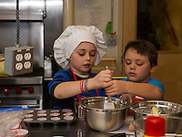 Cameraon Drouin and Aiden Stafford mix their chocolate chip banana muffin batter during cooking class at the Gilford Youth Center on Tuesday afternoon.  (Karen Bobotas/for the Laconia Daily Sun)