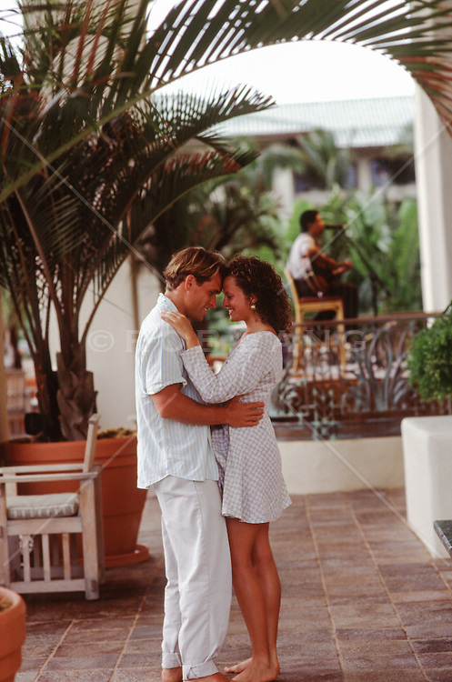 romantic couple on vacation embracing and dancing
