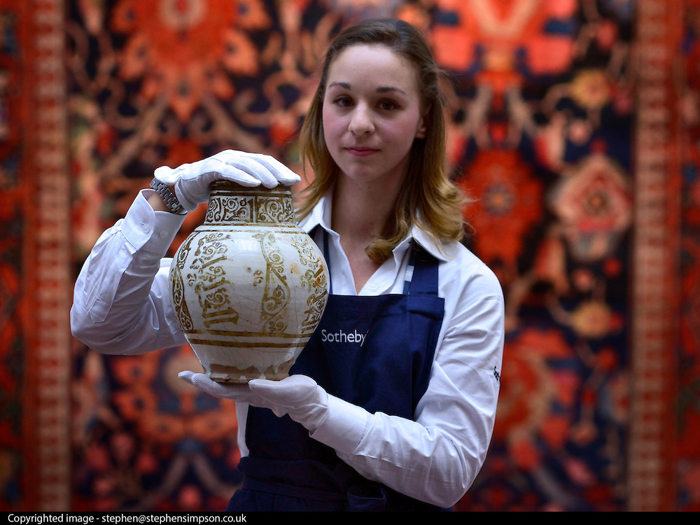 """© Licensed to London News Pictures. 28/09/2012. London, UK Auction room staff hold A highly important Fatimid white-ground lustre pottery jar from Egypt dated 10th/11th century. The jar is expected to fetch 300,000-500,000GBP. Sotheby's Auction rooms in New Bond Street, London hold a photo call for their upcoming """"arts of the Islamic World"""" auction which is expected to realise in the region of 5 million GBP . Photo credit : Stephen Simpson/LNP"""