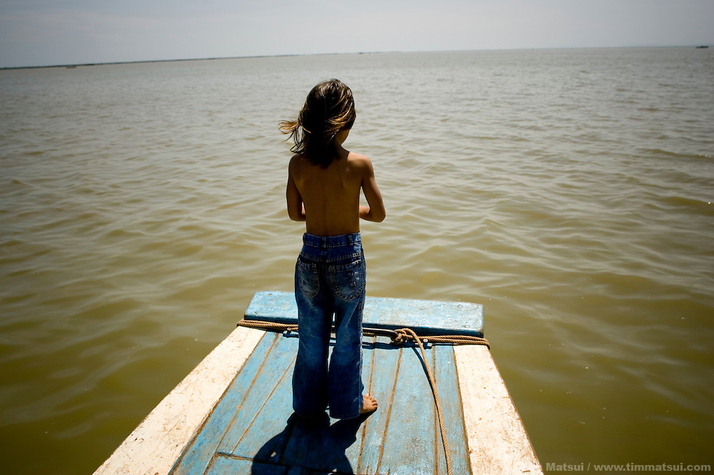 A young Cambodia girl on the bow of a boat.