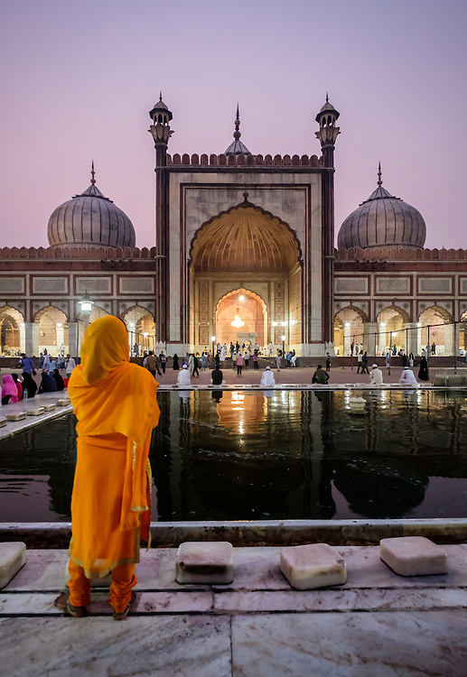 NEW DELHI, INDIA - CIRCA OCTOBER 2016: Woman observing the Jama Masjid mosque in Old Delhi at night. Constructed in red sandstone and white marble the mosque is a popular tourist attraction in Delhi.