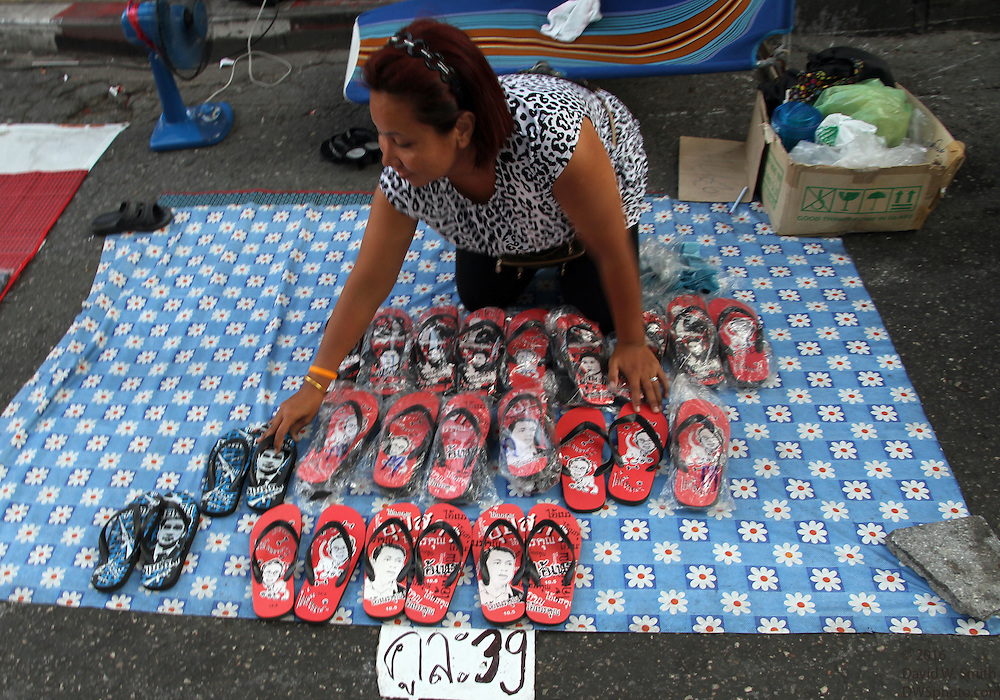 A woman sells sandals decorated with the faces of government leaders during the Red Shirts anti-government protest in the Rachaprasong area of Bangkok.