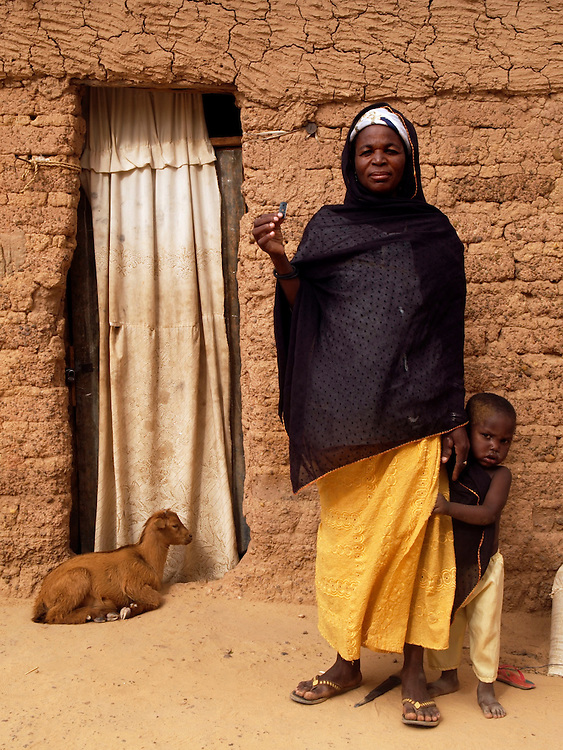 Zeinabou Abdou, 40 - traditional birth attendant stands outside her home with the only instrument she uses in her job - a razorblade. interviewed by Joanna.