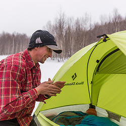 A man sets up a tent while winter camping in New Hampshire's White Mountains. Randolph Community Forest.