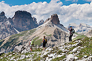 "Walk near Rifugio Locatelli (Dreizinnenhütte) in the Sexten Dolomites Nature Reserve (Parco Naturale Dolomiti di Sesto, or Naturpark Sextner Dolomiten), Italy, Europe. Hike for spectacular views around Tre Cime di Lavaredo (Italian for ""Three Peaks of Lavaredo,"" also called Drei Zinnen or ""Three Merlons"" in German). Until 1919 the peaks formed part of the border between Italy and Austria. Now they lie on the border between the Italian provinces of South Tyrol and Belluno and still are a part of the linguistic boundary between German-speaking and Italian-speaking majorities. The Dolomites were declared a natural World Heritage Site (2009) by UNESCO. Published in Wilderness Travel 2017 Catalog of Adventures."