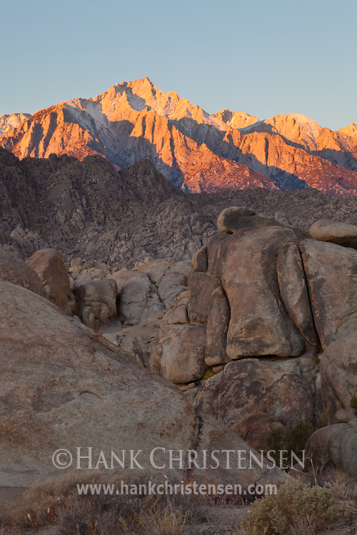 The first light of day lights the distant peaks of the Eastern Sierra, Alabama Hills, CA