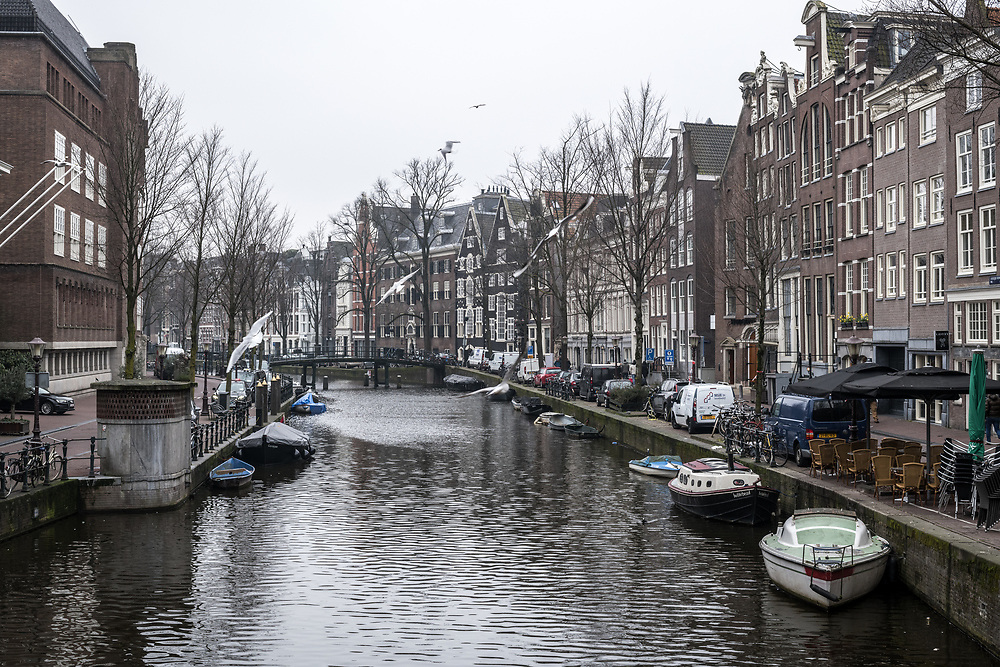 Boats dock on canal with narrow canal houses lining either side, Amsterdam, Netherlands.