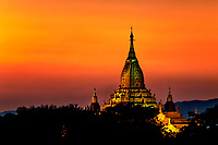 The illuminated Buddhist Ananda Temple shines as a golden jewel, set against the peach-golden sky, Bagan Myanmar.