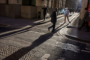 Businessmen walk through winter sunlight on the corner of Lombard Street and Abchurch Lane, EC4, in the City of London.