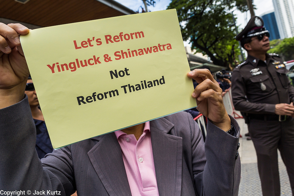 27 AUGUST 2013 - BANGKOK, THAILAND: A Thai protester holds up a sign against Thai Prime Minister Yingluck Shinawatra's political reform commission in front of the British embassy in Bangkok. About 25 people, including at least two British citizens, picketed the embassy Tuesday morning. They were protesting against former British Prime Minister Tony Blair, who is expected to speak to a political reform commission established by Thai Prime Minister Yingluck Shinawatra. The protest leaders were invited in to the Embassy grounds to speak to representative of the British government. The protest disbanded afterwards. No one was arrested during the protest, which lasted a little over an hour.      PHOTO BY JACK KURTZ