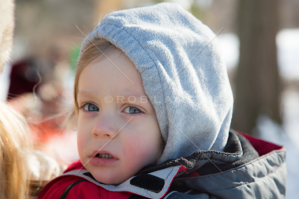 2 year old boy in a hoody and winter coat outdoors