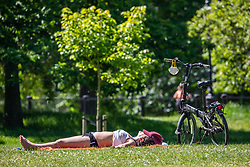 © Licensed to London News Pictures. 20/05/2020. London, UK. A women relaxes in the sunshine in Hyde Park with a mask dangling from her bike as weather experts predict the warmest day of the Year with a high of 27c. Last week the Government eased the law on lockdown to let people spend more time outside to enjoy sunbathing and picnicking. Photo credit: Alex Lentati/LNP