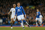 Everton defender Ramiro Funes Mori  shields the ball from Swansea City forward Andre Ayew  during the Barclays Premier League match between Everton and Swansea City at Goodison Park, Liverpool, England on 24 January 2016. Photo by Simon Davies.