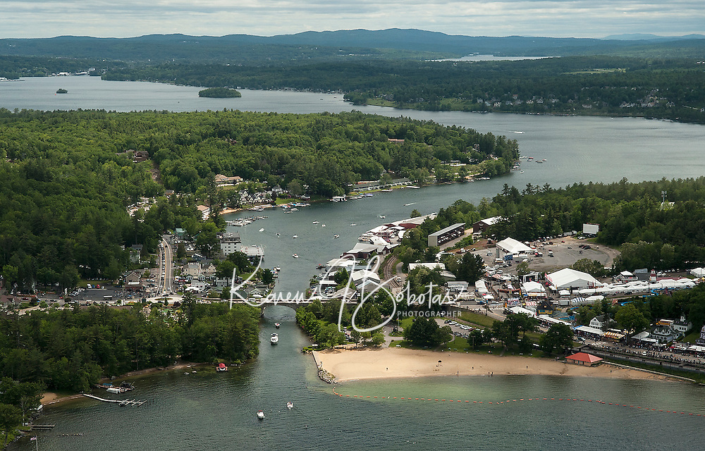 A steady flow of traffic begins to arrive on Saturday for the beginning of Laconia's Motorcycle Week as seen from Lakes Biplane looking down on Weirs Boulevard.  (Karen Bobotas/for the Laconia Daily Sun)