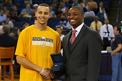 April 10, 2011; Oakland, CA, USA;  Golden State Warriors point guard Stephen Curry (left) is presented with his 2010 FIBA world championship ring by B.J. Johnson (right) before the game against the Sacramento Kings at Oracle Arena.