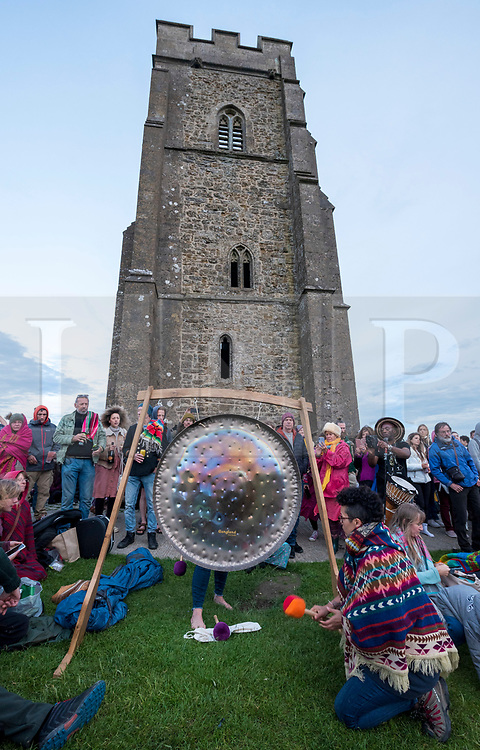 © Licensed to London News Pictures; 20/06/2020; Glastonbury, Somerset, UK. Gongs are played as people gather on Glastonbury Tor for sunset on the Summer Solstice weekend on the longest day of the year today at midsummer. This year due to the coronavirus Covid-19 pandemic and concerns over social distancing at gatherings of people, Stonehenge and Avebury where thousands of people usually gather to celebrate the summer solstice are closed to the public, with the solstice live streamed from Stonehenge. Glastonbury authorities had also asked people to refrain from coming to Glastonbury for the solstice but hundreds came with many staying the night on the Tor. Glastonbury Tor is a hill outside Glastonbury town, topped by the roofless St Michael's Tower, a Grade I listed building which is what remains of the Church of St Michael built in the 14th century. The entire site is managed by the National Trust and has been designated a scheduled monument. Photo credit: Simon Chapman/LNP.