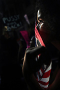 Desiree Rose peers out from behind an American flag during a stand off with Oakland Police during an anti Donald Trump march in Oakland, California.
