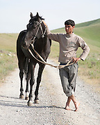 Berdi, head groom at the President of Turkmenistan's Ahal Teke horse complex outside Ashgabat, with a black Ahal Teke stallion