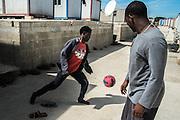 Malta, Hal Far. Open Center. Immigrati giocano a calcio tra i container usati come abitazioni