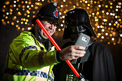 © Licensed to London News Pictures . 16/12/2015 . Manchester , UK . A Greater Manchester Police officer poses for a selfie with Darth Vadar . Star Wars fans attend the midnight screening of Star Wars the Force Awakens at the AMC Great Northern cinema in Manchester City Centre . Photo credit : Joel Goodman/LNP