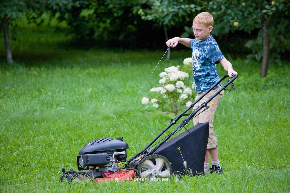 Teenage Boy Pushing Lawn Mower