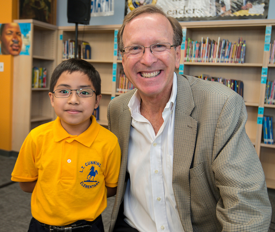 Fourth grader Kevin Rameriz poses for a photograph with Neil Bush following a news conference discussing back to school parenting at Cunningham Elementary School, September 3, 2015.
