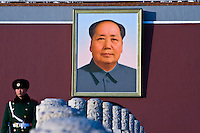 A guard standing in front of Mao's portrait at the entrance to the Forbidden City.