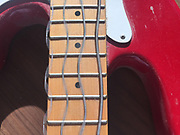 Vibrating strings on a base electric guitar. When plucked, the string vibrates at a specific frequency, which determines the pitch of the note. The vertical lines on the fretboard of the guitar mark where fingers should be placed to shorten or lengthen the vibrating part of the string. Shortening the string produces a note with a higher pitch, lengthening it lowers the note. The image was collected with a digital camera with a fast rolling shutter.