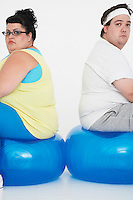 Unhappy overweight man and woman sitting back to back on exercise balls portrait