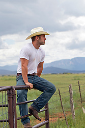 sexy cowboy sitting on a fence at a ranch in New Mexico