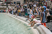 """ROME, ITALY - 20 JUNE 2017: Children put their hands in the Trevi fountain, though it is prohibited, in Rome, Italy, on June 20th 2017.<br /> <br /> The warm weather has brought a menacing whiff of tourists behaving badly in Rome. On April 12, a man went skinny-dipping in the Trevi fountain resulting in a viral web video and a 500 euro fine.<br /> <br /> Virginia Raggi, the mayor of Rome and a national figurehead of the anti-establishment Five Star Movement,  issued an ordinance involving harsher fines for eating, drinking or sitting on the fountains, for washing animals or clothes in the fountain water or for throwing anything other than coins into the water of the Trevi Fountain, Bernini's Four Fountains and 35 other city fountains of artistic or historic significance around the city.  """"It is unacceptable that someone use them to go swimming or clean themselves, it's an historic patrimony that we must safeguard,"""" Ms. Raggi said."""