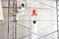 Two manual painters working in commercial space