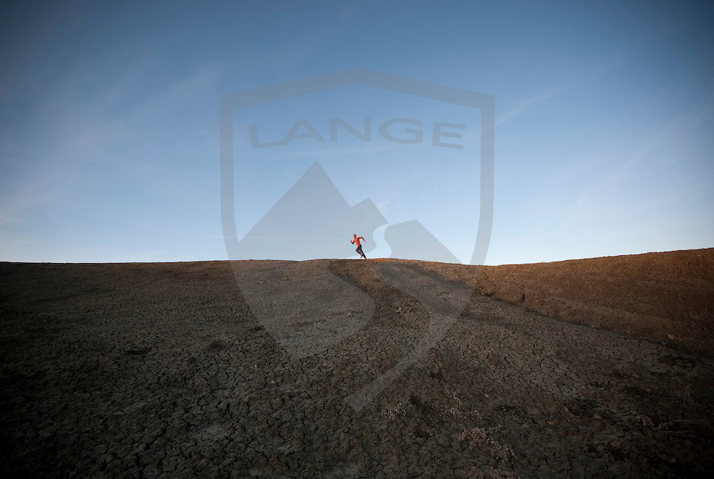 abstract composition of man running with red shirt underneath a  blue sky on top of a dark desert mesa with sunset light.  taken in the ojito wilderness at white mesa, new mexico.