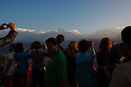 Tourists take in the sunrise view of the Himalayan peaks from Sarangkot near Pokhara, Nepal.
