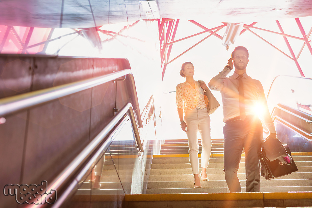 Business people walking downstairs with lens flare in background