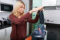 Young blond woman juicing carrots in kitchen