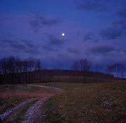 Moonrise in November with a farm field and tractor track