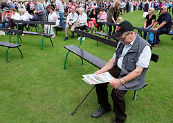 © Licensed to London News Pictures.14/07/15<br /> Harrogate, UK. <br /> <br /> A man reads the paper while other visitors gather to see during HRH The Prince of Wales and the Duchess of Cornwall during their visit on the opening day of the Great Yorkshire Show.  <br /> <br /> England's premier agricultural show opened it's gates today for the start of three days of showcasing the best in British farming and the countryside.<br /> <br /> The event, which attracts over 130,000 visitors each year displays the cream of the country's livestock and offers numerous displays and events giving the chance for visitors to see many different countryside activities.<br /> <br /> Photo credit : Ian Forsyth/LNP
