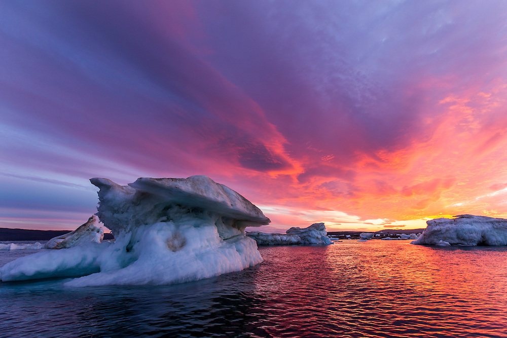 Canada, Nunavut, Territory, Setting midnight sun lights clouds above melting iceberg in Hurd Channel near Vansittart Island's Cape Shackleton just south of Arctic Circle