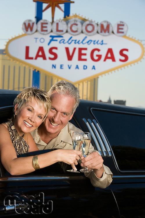 Middle-aged couple in limousine in front of  Welcome to Las Vegas sign, portrait