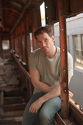 Man seated in a broken down window of a train
