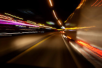 lights reflect off the sde of a tractor trailor truck as it speeds on a highway at night.