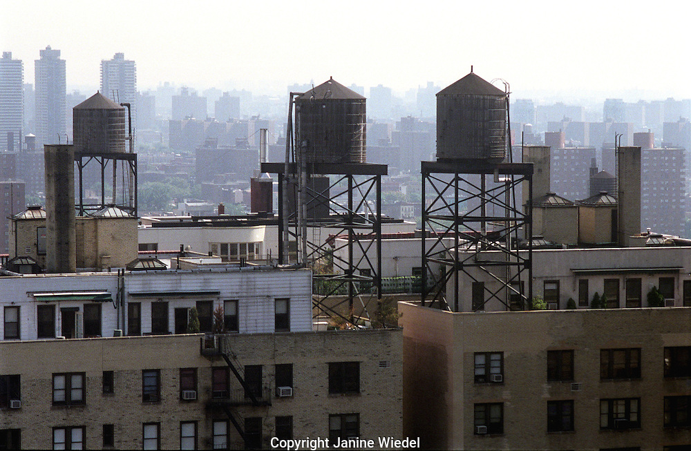 New York rooftop scene with water tanks on to of buildings.
