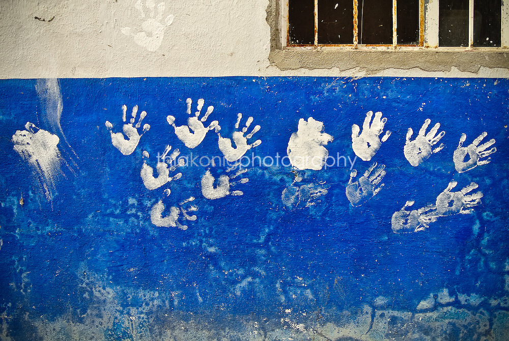 White hand prints painted on a blue wall, San Blass, Mexico