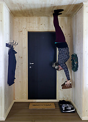An employee hangs in the hallway in 'The Upside Down House', a zero-gravity illusion experience, in The Triangle in Bournemouth, Dorset.