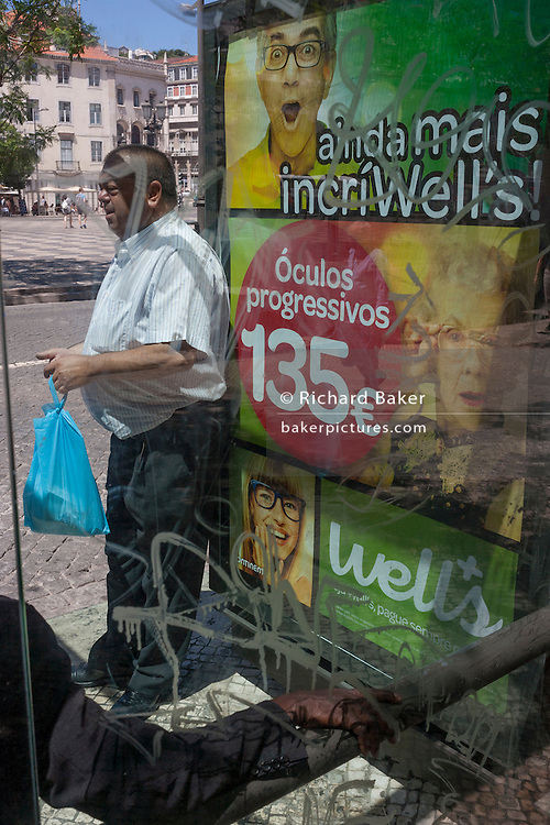 A Lisbon bus passenger awaits his transport in front of a spectacles ad for the Portuguese retailer Well's.