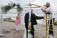Cherie Richmond (left), Scott Thatcher, and Tim Richmond decorate the gazebo for the wedding of Katie Richmond in Jupiter, Florida, on January 20, 2018.